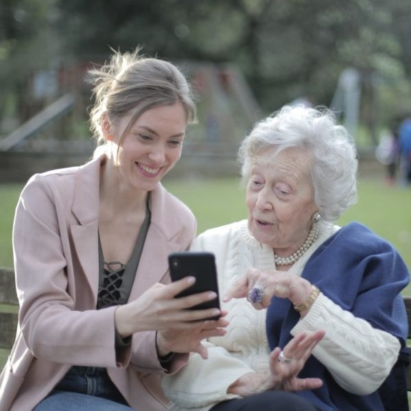 Senior mother and adult daughter using smartphone